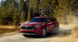 A red 2021 Toyota Highlander Hybrid is driving on a dirt road with bikes on the roof rack.