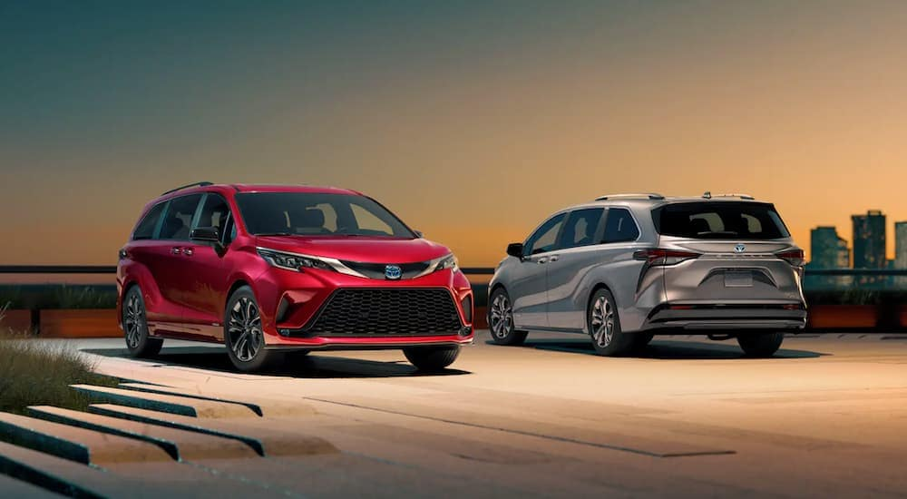 A red and a silver 2021 Toyota Sienna Hybrid are parked at sunset in front of a city skyline.