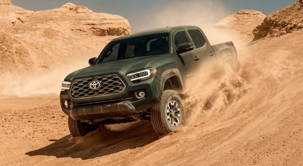 A green 2021 Toyota Tacoma is off-roading in sand.