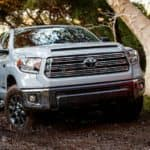 A silver 2021 Toyota Tundra, the larger of the Toyota pickup trucks, is off-roading in the woods.