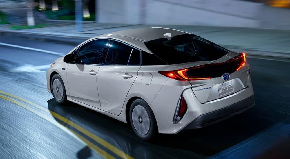 A silver 2021 Toyota Prius LE is driving on a city street at night.