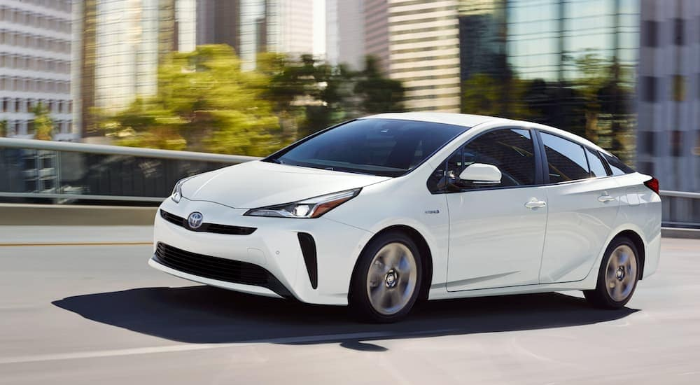 A white 2021 Toyota Prius Limited is driving on a highway past a city.