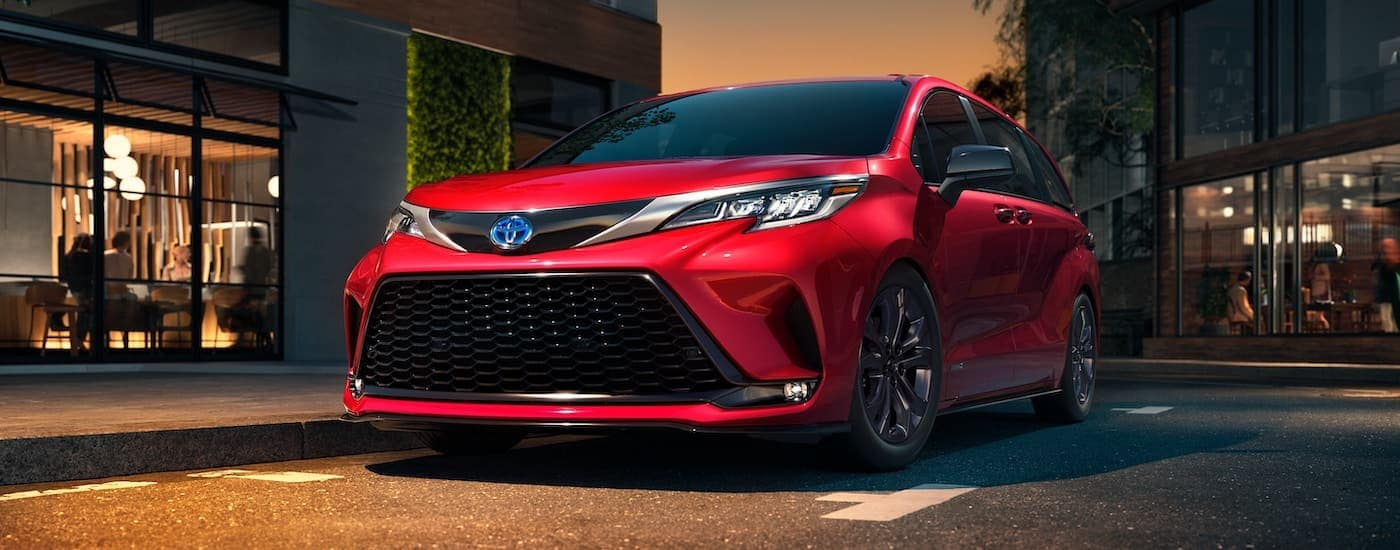 A red 2021 Toyota Sienna is parked in the city at dusk.