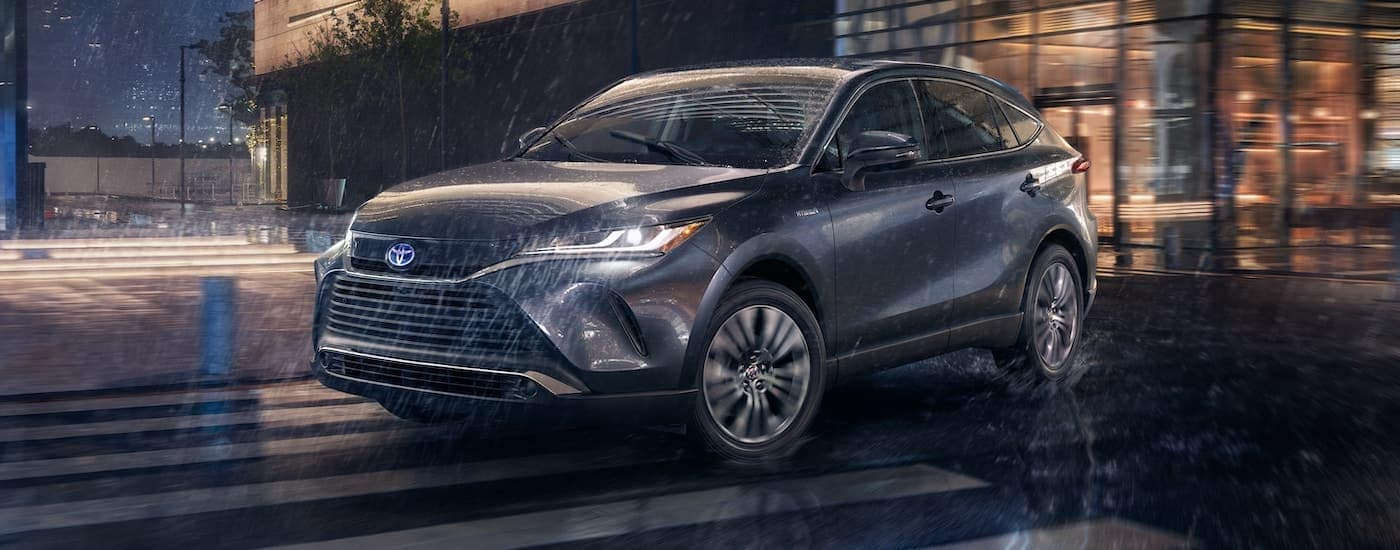 A dark grey 2021 Toyota Venza is shown from the side driving in the rain.