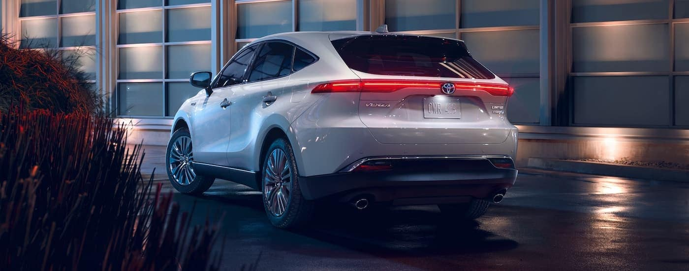 A white 2021 Toyota Venza is shown from the rear with the tail lights illuminated.