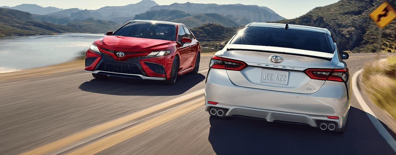 A white and a red 2021 Toyota Camry are passing each other next to a lake and mountains.
