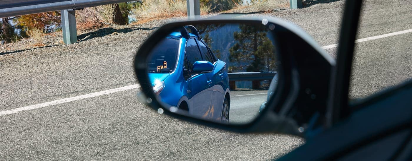 A close up shows the illuminated blind spot monitoring icon on a 2021 Toyota Prius.