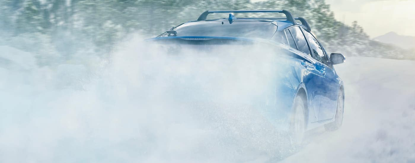 A blue 2021 Toyota Prius is shown from the rear kicking up snow after winning the 2021 Toyota Prius vs 2021 Honda Insight comparison.
