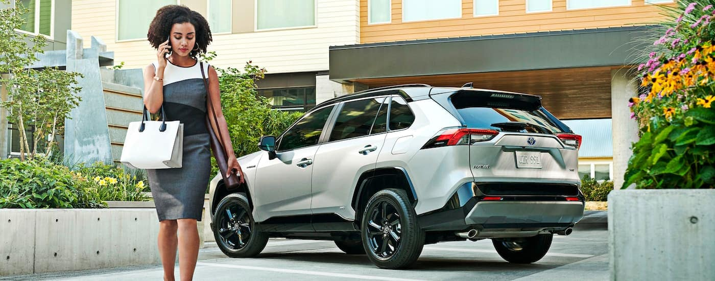 A woman talking on a cell phone is shown walking away from a silver 2021 Toyota RAV4.