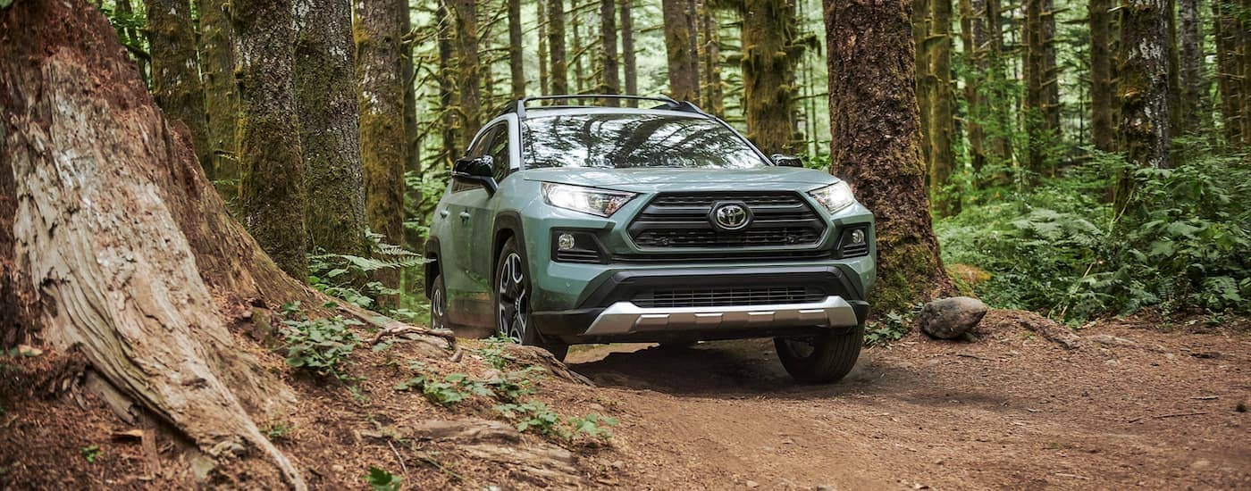 A pale green 2021 Toyota RAV4 is driving through the woods after winning the 2021 Toyota RAV4 vs 2021 Honda CR-V competition.