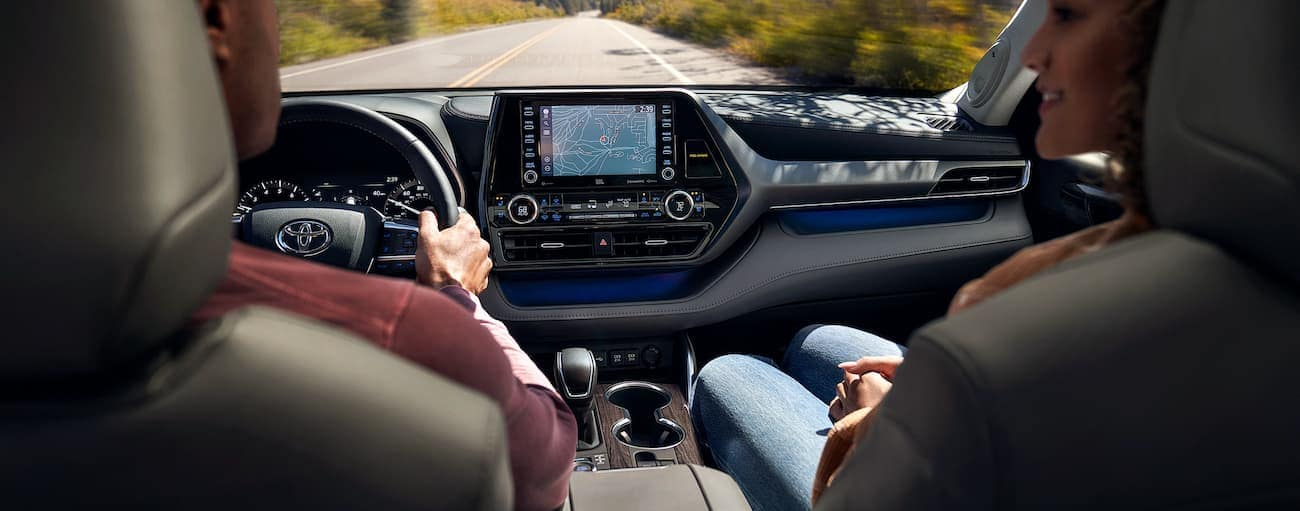 Two people are in the front seats of a 2021 Toyota Highlander with navigation on the screen.