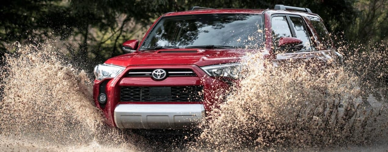 A red 2021 Toyota 4Runner TRD Off-Road Premium is shown splashing through a large puddle.