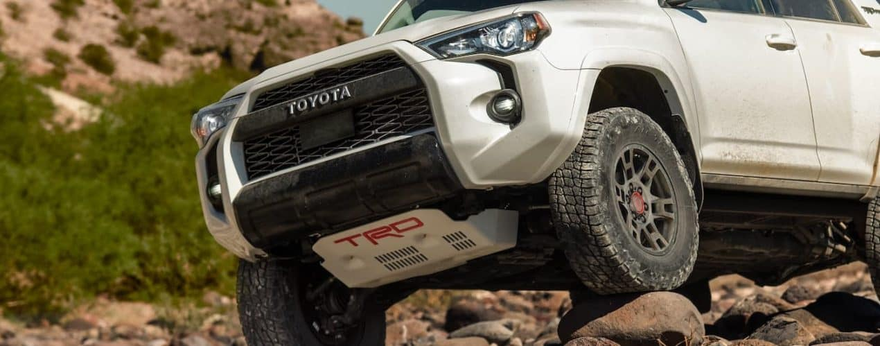 A white 2021 Toyota 4Runner TRD Pro is shown driving over a rock pile from a low angle.