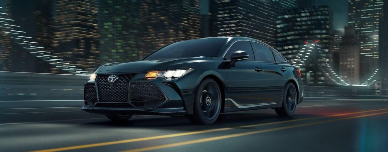 A black 2021 Toyota Avalon XSE Nightshade Edition is shown from the side driving through a city at night.