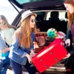 A group of teenage friends is shown unloading an SUV during a road trip.