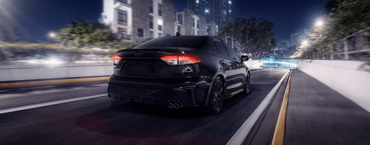A black 2021 Toyota Corolla SE Nightshade Edition is shown from the rear driving through a city.