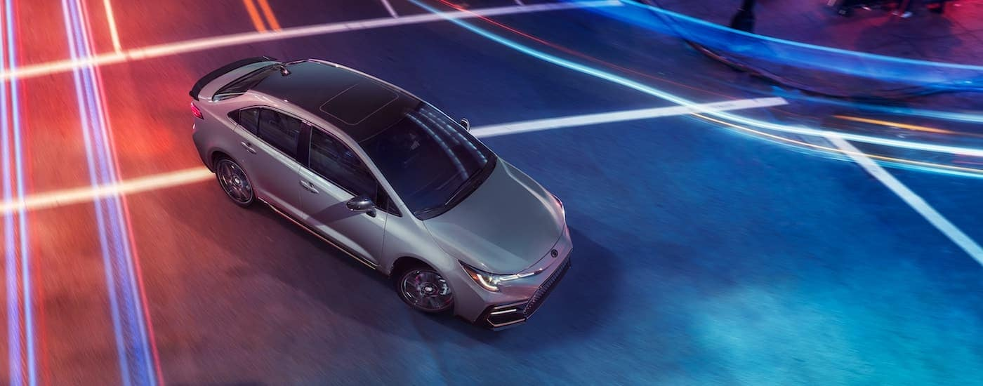 A silver 2021 Toyota Corolla XSE Apex Edition is shown from a high angle driving through an intersection after leaving a PA Toyota Corolla dealer.