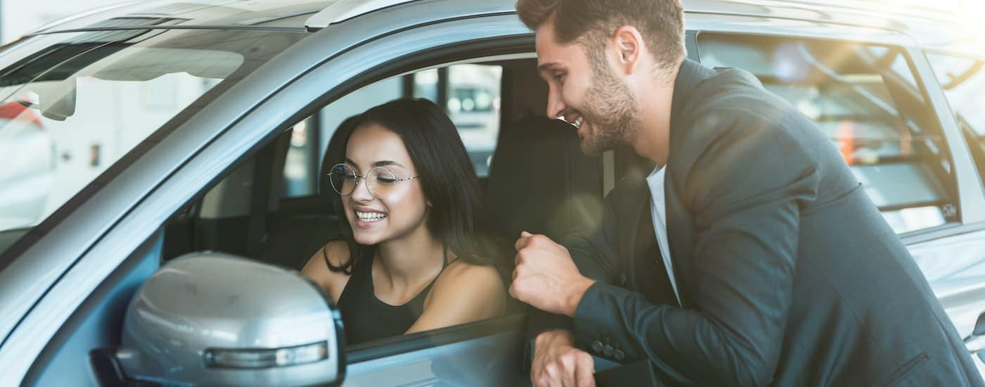 A close up shows a salesman smiling and talking to a woman in a car.