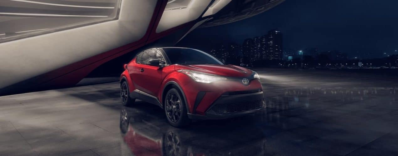 A red 2021 Toyota C-HR Nightshade Edition is shown with its headlights on under a futuristic structure.