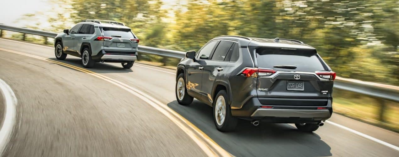 A dark grey and a light blue 2021 Toyota RAV4 are driving toward a corner on a road past trees.