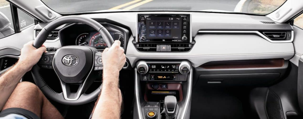 Hands are on the steering wheel of a 2021 Toyota RAV4, shown from the interior.