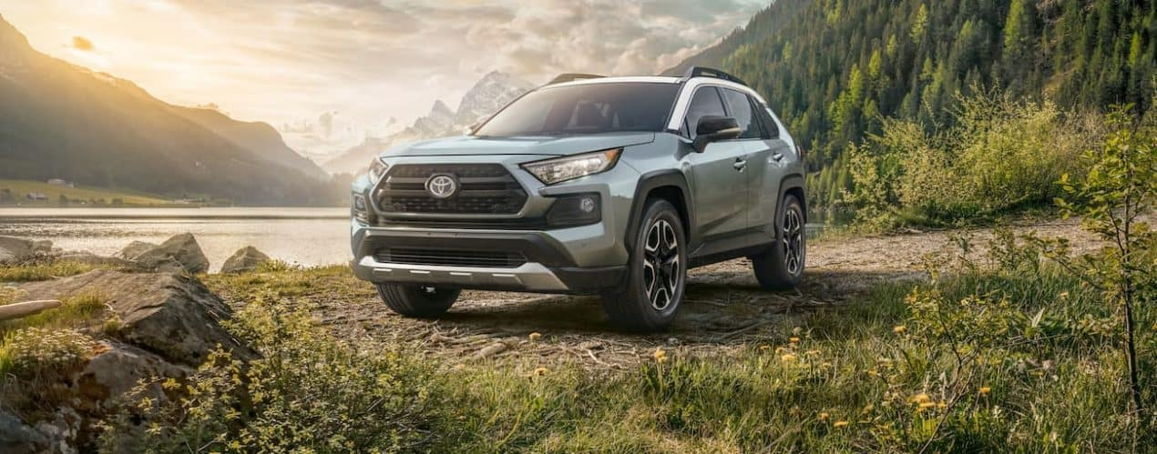 A light green 2021 Toyota RAV4 is parked in front of a lake and mountains.