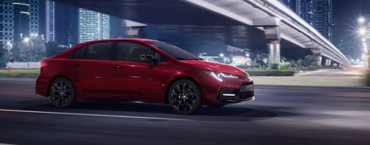 A red 2022 Toyota Corolla SE Nightshade is shown from the side driving through a city at night.