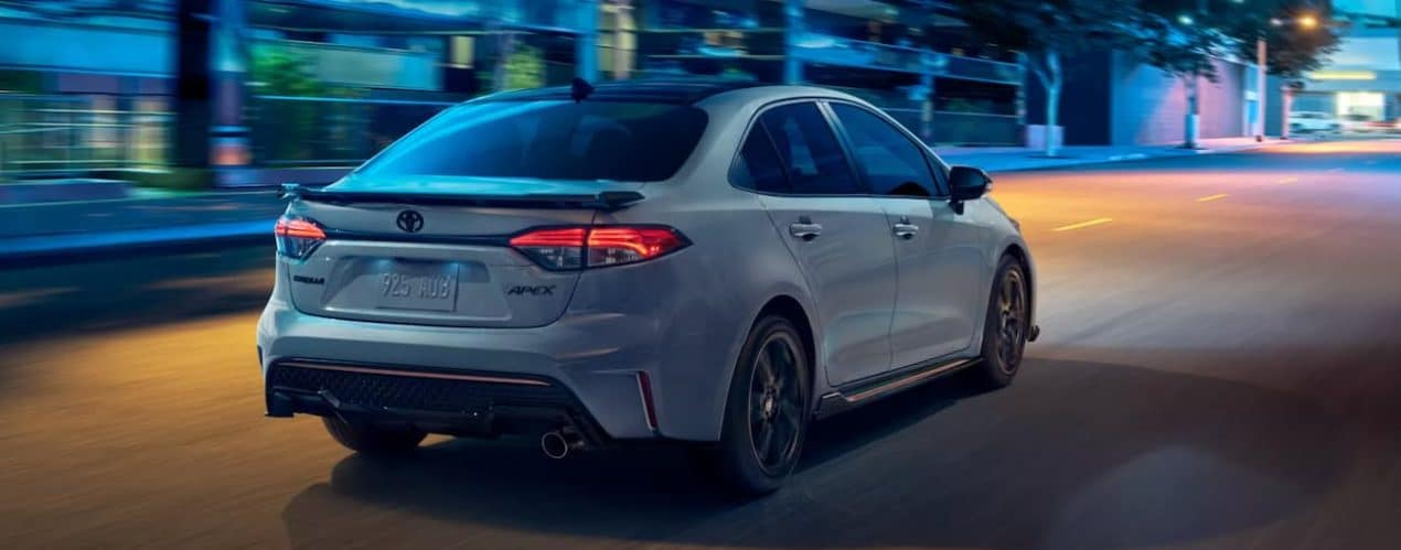 A blue 2022 Toyota Corolla XSE Apex is shown from the rear driving through a city at night.