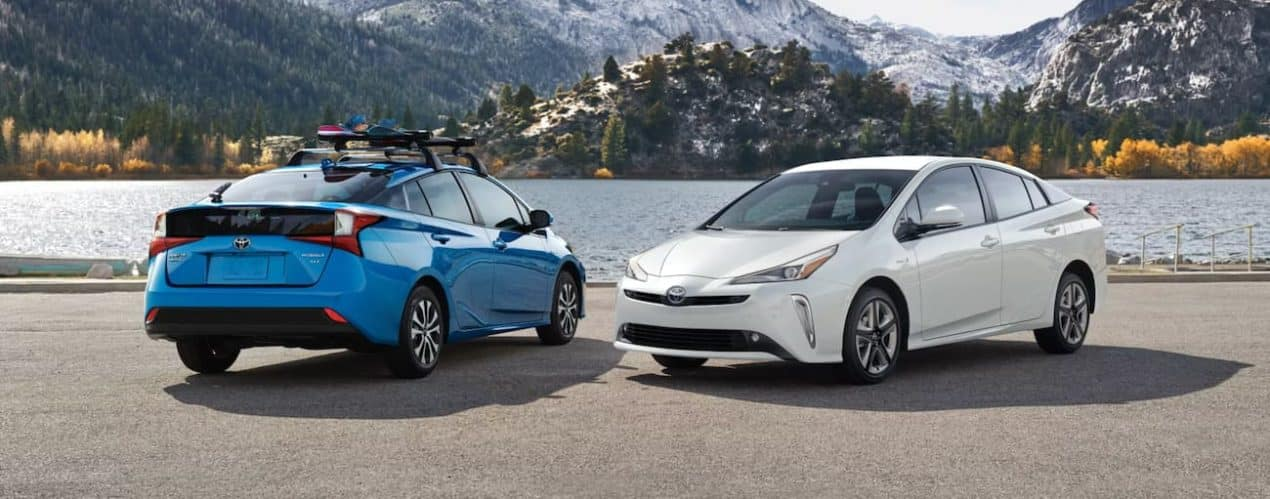 A blue and a white 2022 Toyota Prius XLE AWD are shown parked in front of a lake.