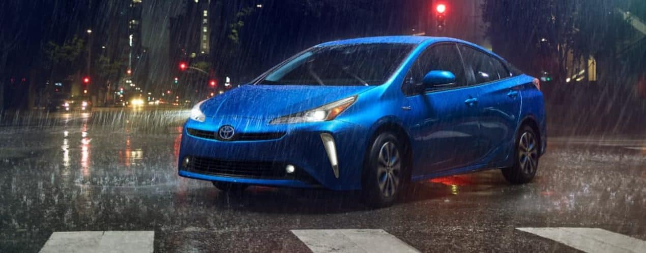 A blue 2022 Toyota Prius XLE AWD is shown driving through a city in the rain.