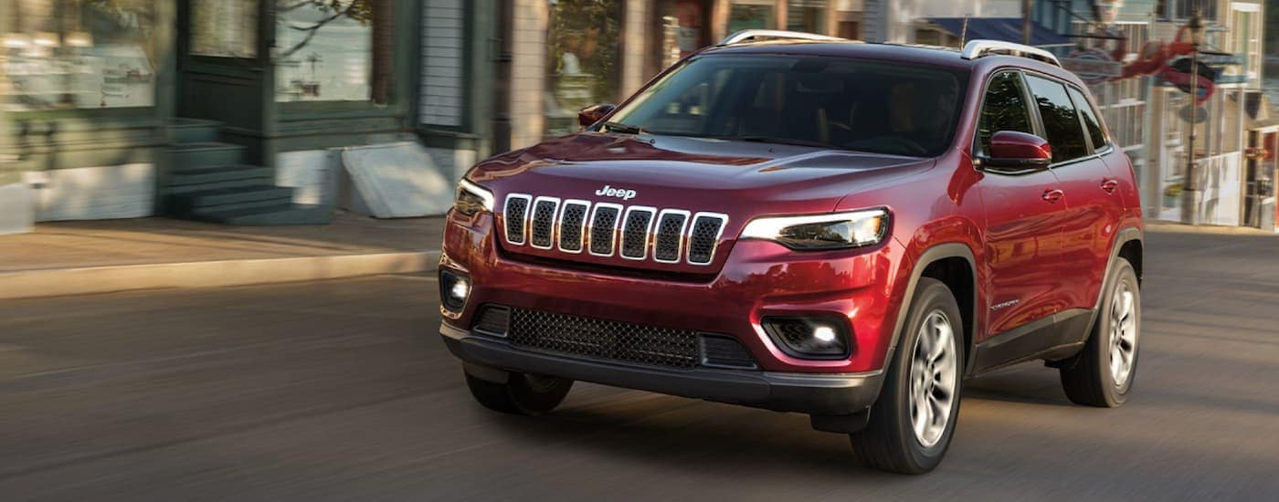 A red 2020 Jeep Cherokee is driving on a city street near Defiance, OH.