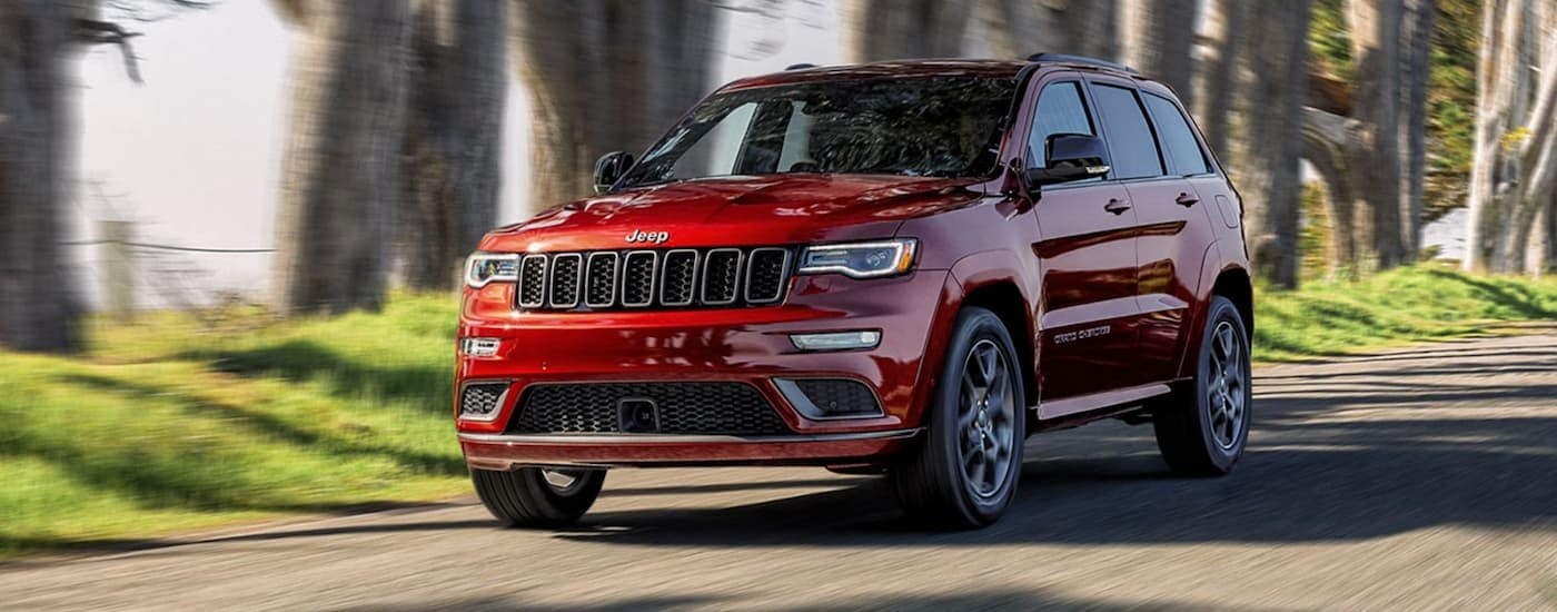 A red 2020 Jeep Grand Cherokee is driving on a tree-lined road.