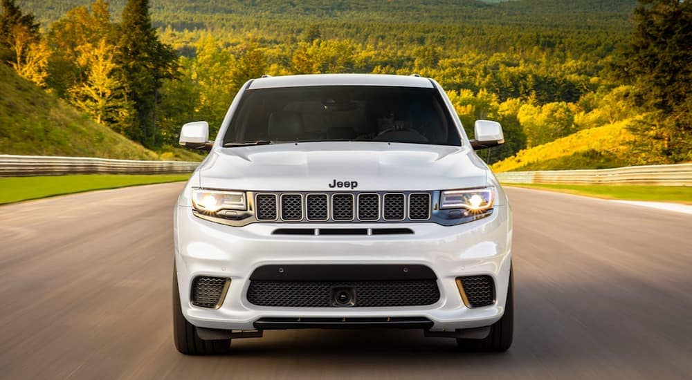 A white 2020 Jeep Grand Cherokee is shown from the front driving on a highway after leaving a Jeep dealership near me in Defiance, OH.
