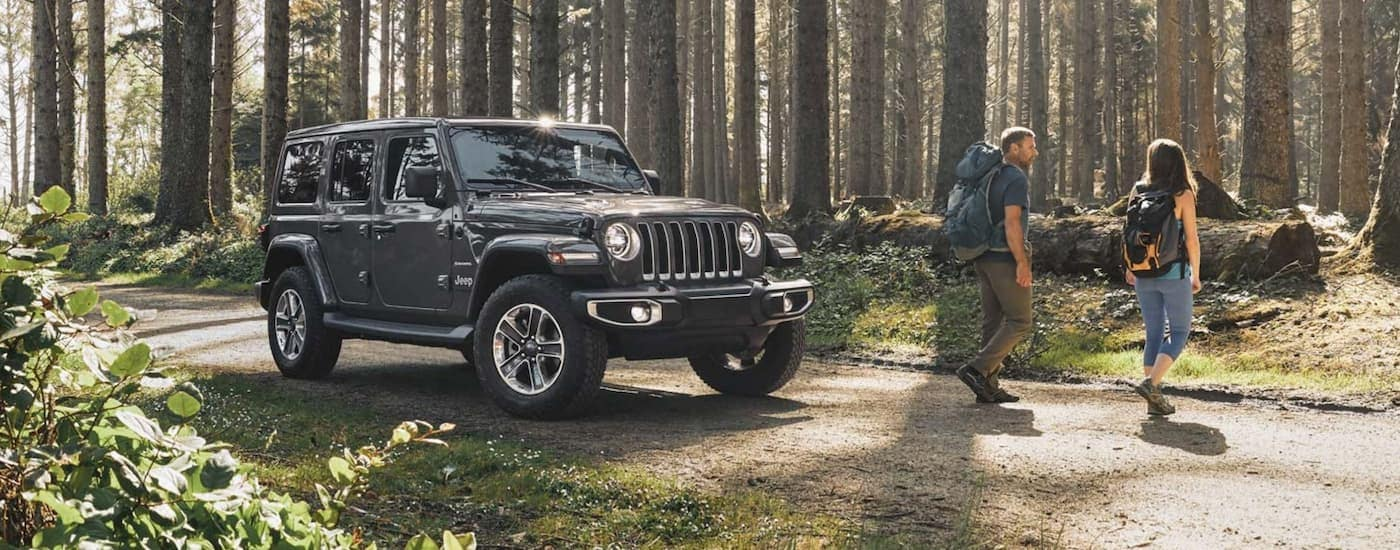 A grey 2020 Jeep Wrangler Unlimited is parked on a trail as a couple walks away to go hiking.