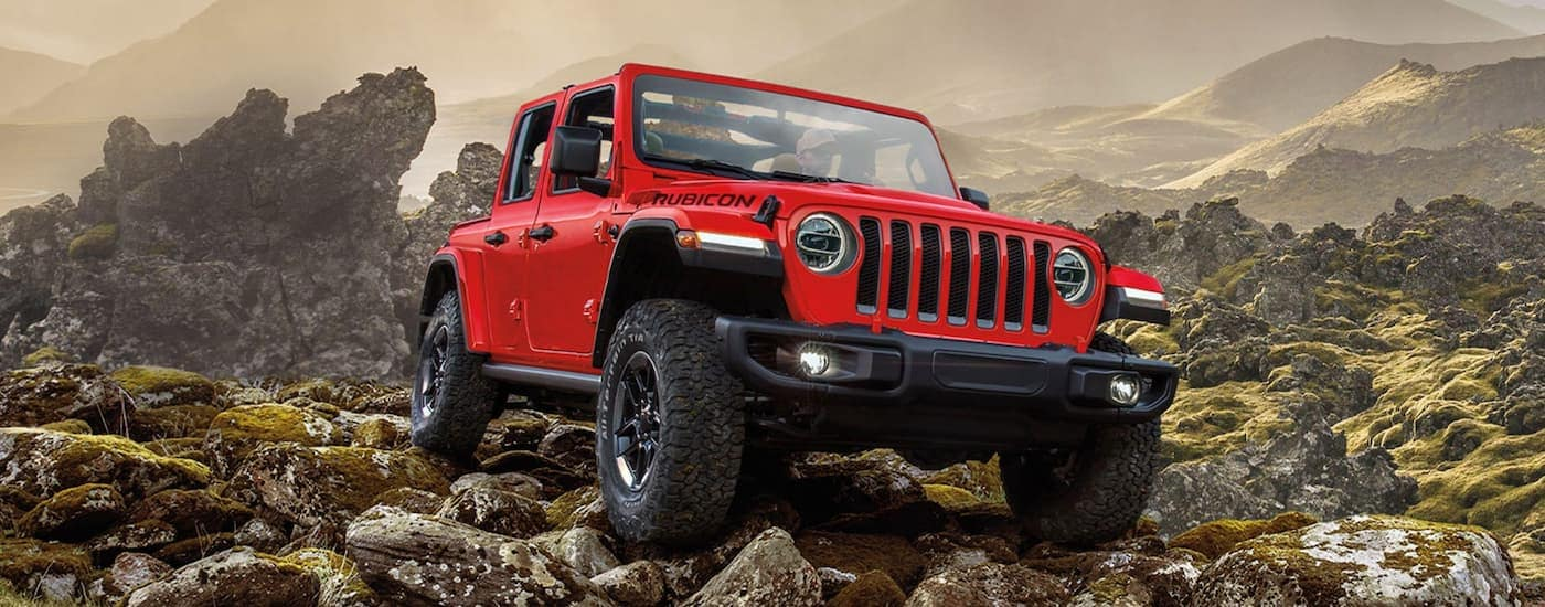 A red 2020 Jeep Wrangler Unlimited is off-roading on rocky terrain.