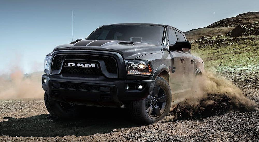 A used 2019 Ram 1500 Classic Warlock kicking up dirt on a trail after leaving a Used Car Dealership in Defiance, OH.