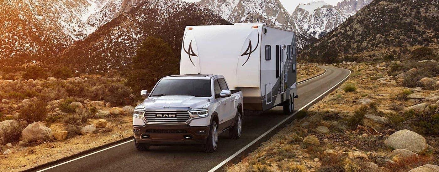 A white 2019 Ram 1500 towing a white trailer through a mountain highway.
