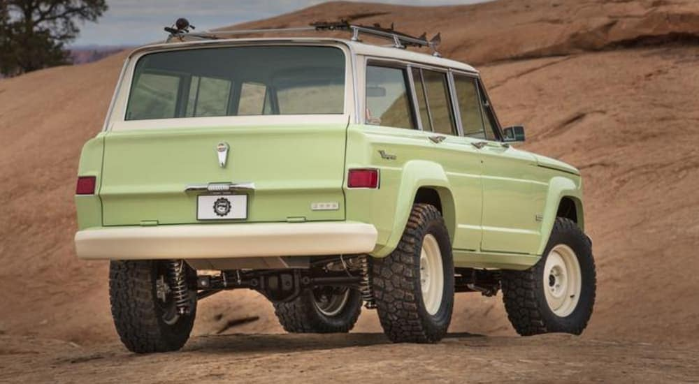 A light green Jeep Wagoneer Roadtrip Concept is shown from the rear in the desert.