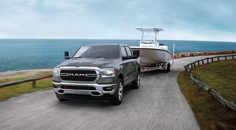 A gray 2020 Ram 1500 from a Ram dealer near me is towing a boat along the coast.