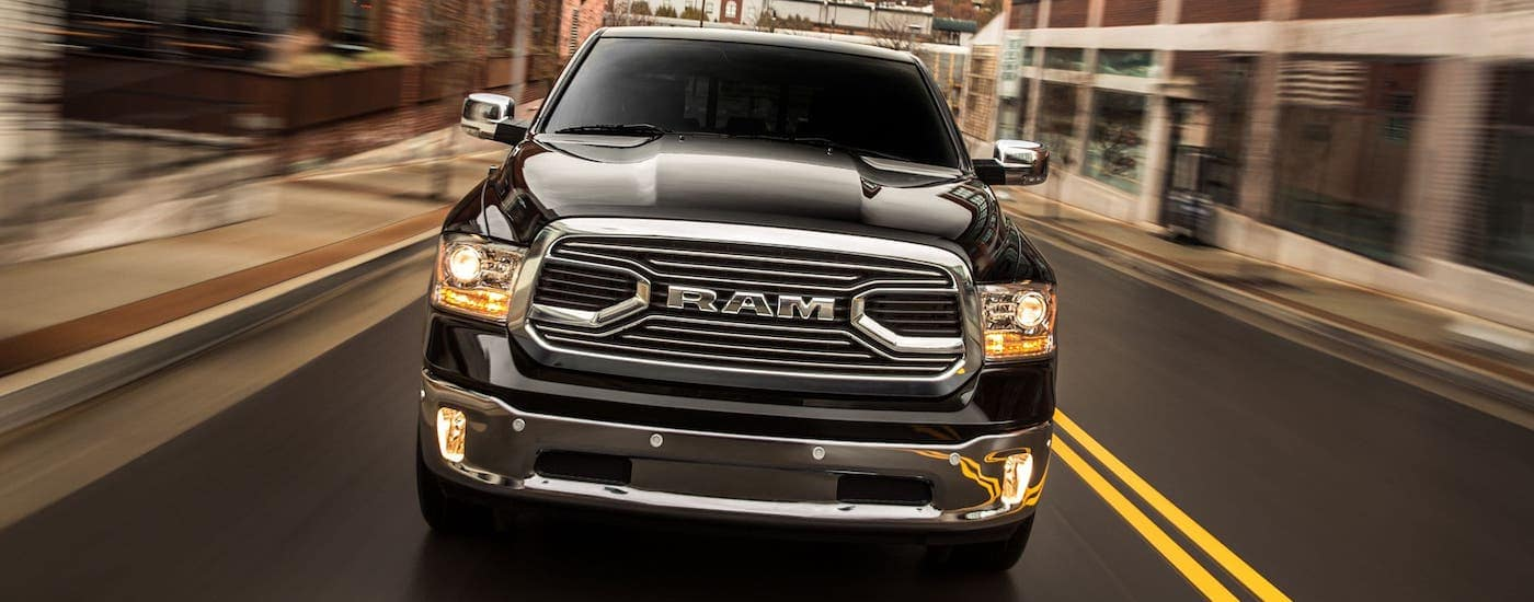 A black 2016 Ram 1500 is shown from the front driving on a Defiance, OH, street.