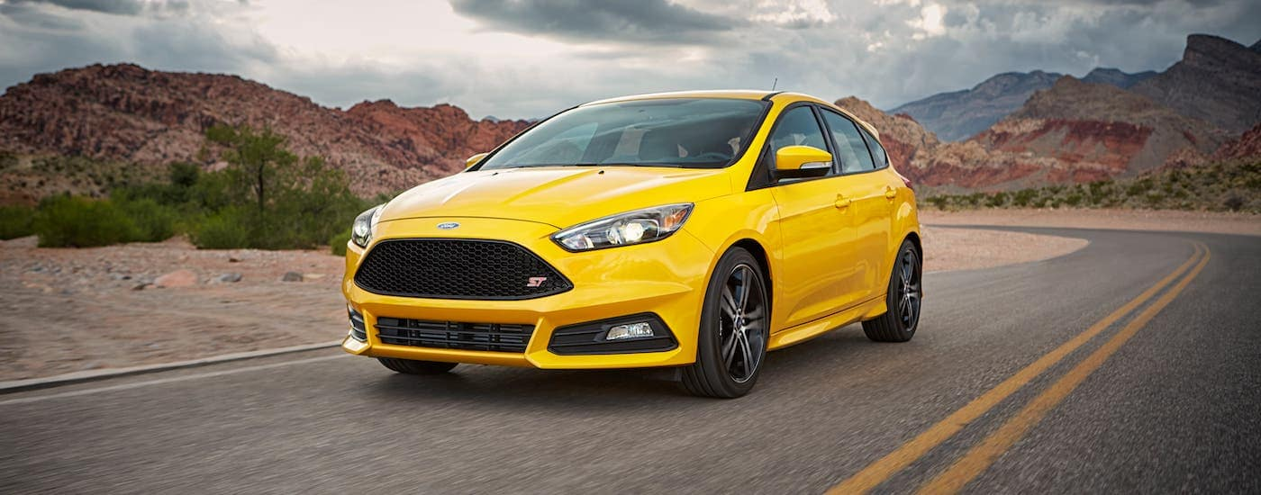 A yellow 2017 Ford Focus ST is driving on a desert highway.