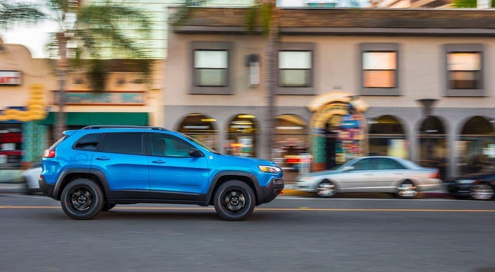 A blue 2019 Jeep Cherokee Trailhawk is driving on a city street.