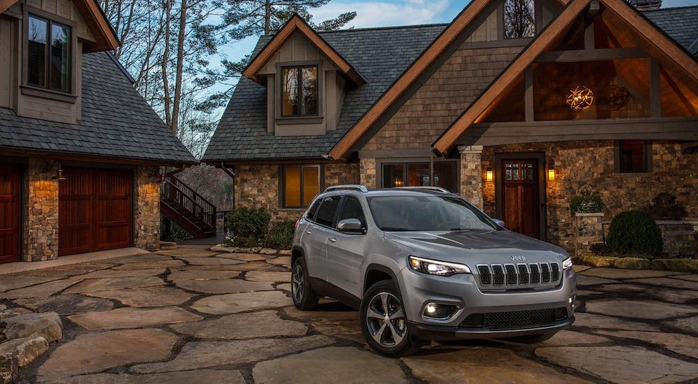 A silver 2019 Jeep Cherokee from a used car dealer near me is parked in front of a stone home.