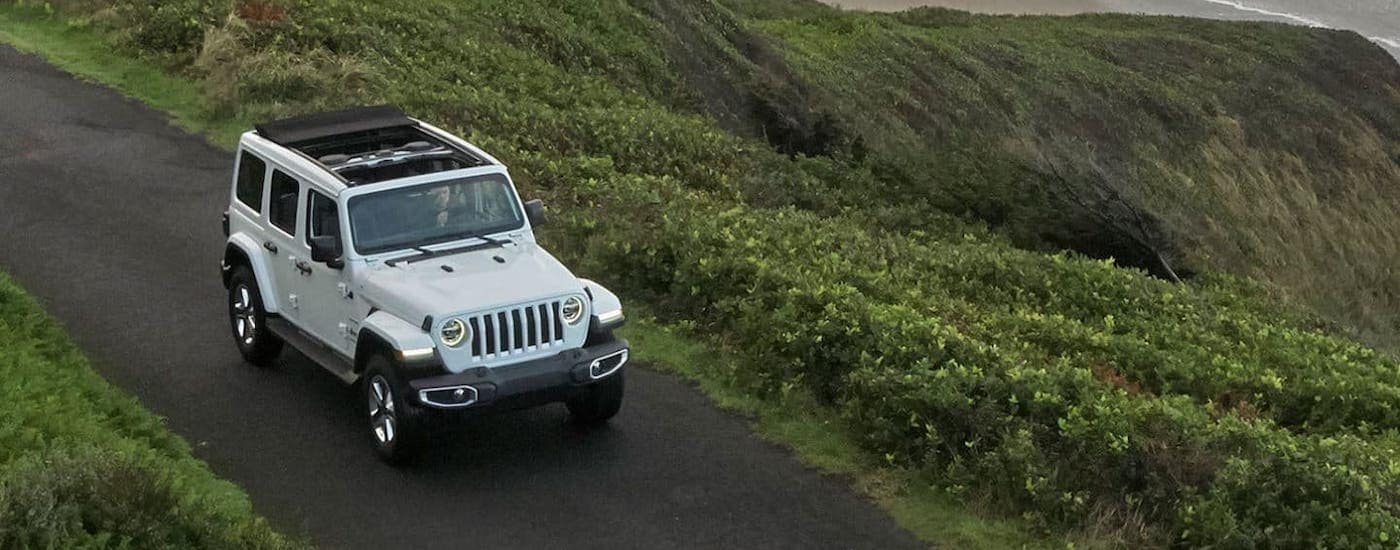 A white 2020 Jeep Wrangler Unlimited is driving over a lake near Defiance, OH.