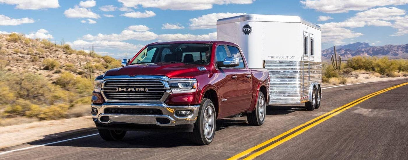 A red 2020 Ram 1500 is towing a trailer after getting a 5-minute car loan near Defiance, OH.