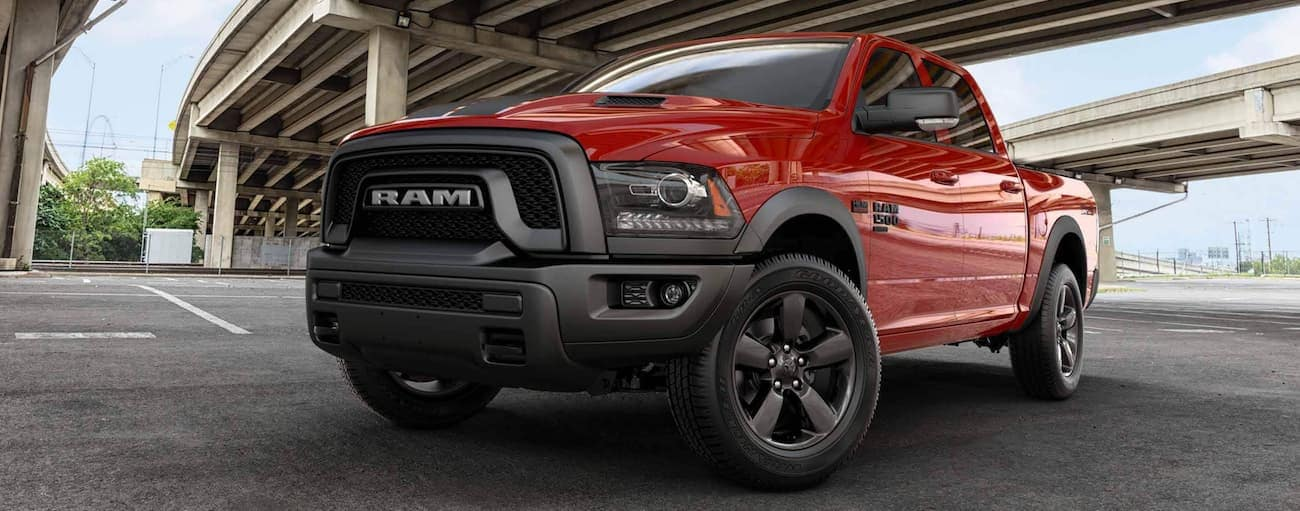 A red 2020 Ram 1500 Classic is parked under a city overpass.