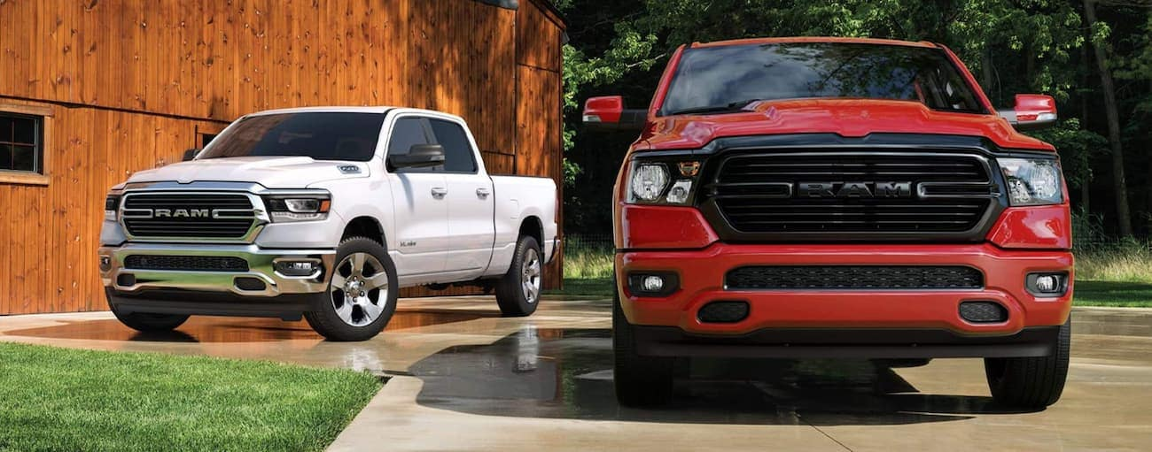 A red 2020 Ram 1500 is parked in front of a white one with a wooden barn behind them near Defiance, OH.