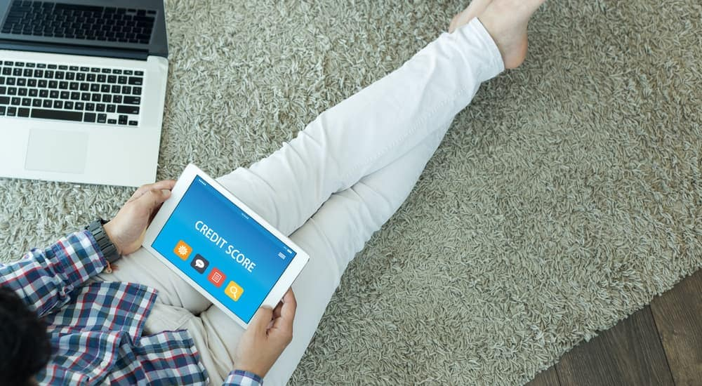 A person is sitting on the floor with a tablet displaying a credit score website.