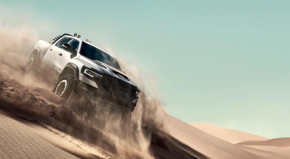 A silver 2021 Ram 1500 TRX, that will be available at a Ram dealer soon, is off-roading on a sand dune.