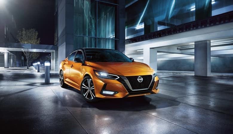 An orange 2020 Nissan Sentra parked outside at night - Fiesta Nissan in Edinburg, TX